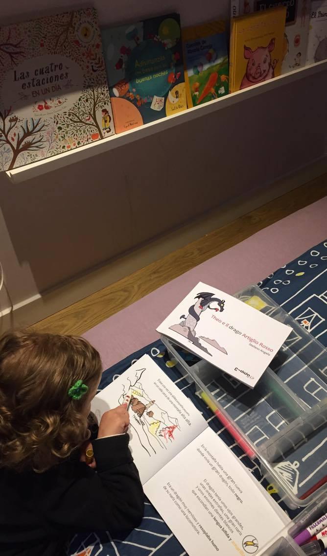 """Una bambina legge e colora il libro """"Theo e il drago Artiglio Rosso"""""""